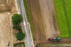 Vista aérea vertical abstrata de uma estrada secundária estreita na borda de uma área da terra arável com as listras coloridas di fotografia de stock royalty free