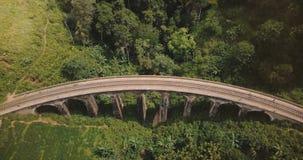 Vista aérea, zangão que desce sobre os turistas que andam na ponte Ella de nove arcos em Sri Lanka, vista famosa da arquitetura video estoque