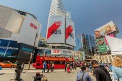 vista abajo de la calle joven de Toronto de la ciudad con los diversas edificios, carteleras y la gente modernos caminando en fon Foto de archivo libre de regalías