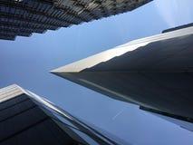 Vista abstracta de la arquitectura moderna con un avión que pasa por encima en Londres imagenes de archivo