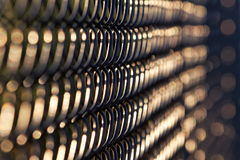 Vista abstrata da cerca preta do elo de corrente na luz solar da noite Fotografia de Stock