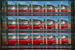 Vista abstrata de um carro vermelho visto através de um tijolo de vidro Fotografia de Stock Royalty Free