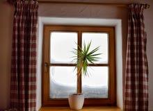 Vista accogliente dalla finestra del chalet alpino un giorno di inverno nevoso Vista dall'interno immagine stock libera da diritti