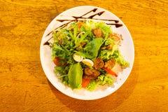 A vista acima da salada consistiu nos tomates, na carne, nos ovos e na rúcula decorados com o molho marrom colocado sobre fotos de stock