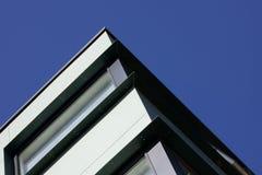 Vista acima em um canto de um grupo de construção de aço moderno contra um céu azul torrado imagem de stock royalty free