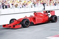 Vista ad angolo della macchina da corsa rossa di sport di motore che accelera giù la pista che conduce il pacchetto con mosso e f Fotografia Stock