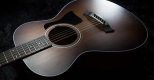 Vista ad angolo di una chitarra acustica Scuro-boscosa Fotografia Stock