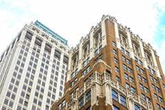 Vista ad angolo su ai vecchi edifici per uffici alti decorati dal livello della via Immagine Stock Libera da Diritti