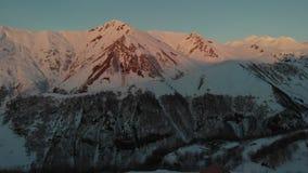 Vista aerea alla chiesa in montagne di inverno ad alba archivi video