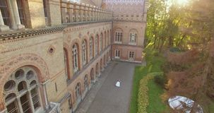 Vista aerea: belle coppie che camminano al grande castello antico 4k nel tramonto video d archivio