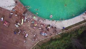 Vista aerea che gira su sopra lo stagno con un acquascivolo e molti gente ed adolescenti durante il partito che vanno a fare una  archivi video
