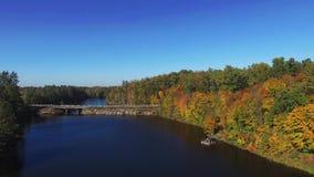 Vista aerea che sorvola il bello fiume di autunno con il ponte e la foresta archivi video