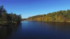 Vista aerea che sorvola il bello fiume di autunno con il ponte e la foresta stock footage