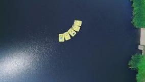 Vista aerea che zuma da alcuni paddeleboats che galleggiano sul lago nei precedenti scenici 4K stock footage