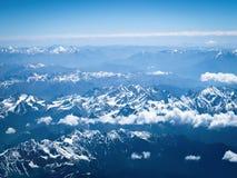 Vista aerea dall'aeroplano, dalle nuvole e dalla neve sopra la montagna immagini stock