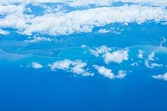 Vista aerea dalla finestra dell'aeroplano, cloudscape, linea costiera, terra da sopra Immagini Stock Libere da Diritti