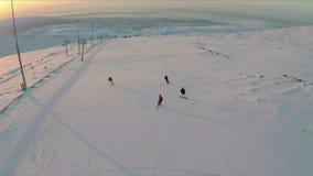 Vista aerea degli sciatori e degli snowboarders al tramonto archivi video