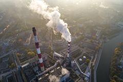 Vista aerea dei camini di fumo della pianta e dello smog di CHP sopra la città e dei builidings nei precedenti fotografia stock libera da diritti