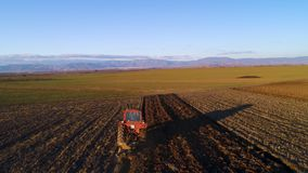 Vista aerea dei campi del raccolto con il trattore Agricoltore che ara campo di stoppie archivi video
