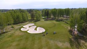 Vista aerea dei giocatori di golf che giocano sul verde mettente Giocatori professionali su un campo da golf verde Immagini Stock Libere da Diritti