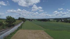 Vista aerea dei terreni coltivabili e della campagna con un binario ferroviario un bello giorno di estate soleggiato video d archivio