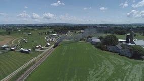 Vista aerea dei terreni coltivabili e della campagna con un treno a vapore d'annata archivi video