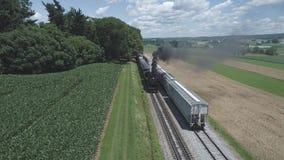 Vista aerea dei terreni coltivabili e della campagna con un treno a vapore d'annata stock footage