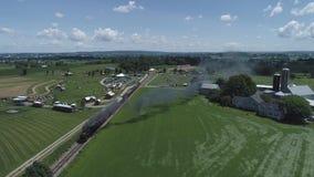 Vista aerea dei terreni coltivabili e della campagna con un treno a vapore d'annata video d archivio