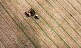Vista aerea del campo del raccolto con il trattore e l'associazione Fotografia Stock