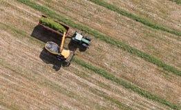 Vista aerea del campo del raccolto con il trattore e l'associazione Fotografie Stock