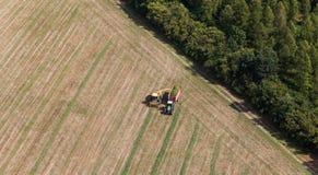 Vista aerea del campo del raccolto con il trattore e l'associazione Fotografie Stock Libere da Diritti