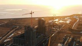 Vista aerea del cantiere con le gru di costruzione al tramonto immagini stock