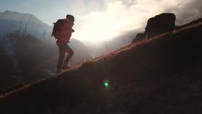 Vista aerea del colpo epico di una ragazza che cammina sull'orlo della montagna come siluetta in un bello tramonto Siluetta stock footage