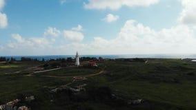 Vista aerea del faro e del mare nell'orizzonte con cielo blu ed erba verde Il Cipro Pafo video d archivio
