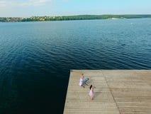Vista aerea del fiume e del pilastro Due ragazze cantano sul pilastro Trama surreale immagini stock
