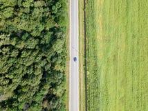 Vista aerea del fuco delle automobili commoventi sulla strada campestre con Forest And Agriculture Crop Field immagine stock