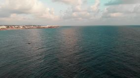 Vista aerea del fuco di piccola navigazione bianca della barca attraverso l'oceano che lascia area di località di soggiorno dietr stock footage