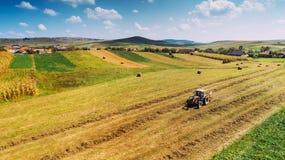 Vista aerea, vista del fuco di raccolta di agricoltura Il lavoratore e l'agricoltore che per mezzo del trattore sul raccolto pota fotografia stock libera da diritti