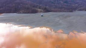 vista aerea del fuco 4k, catastrofe ecologica, chiesa sommersa sotto l'acqua dei rifiuti minerari video d archivio