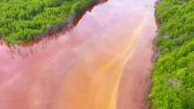 Vista aerea del fuco 4k dell'acqua di rame rossa variopinta dei rifiuti minerari contrariamente alla foresta verde fresca archivi video