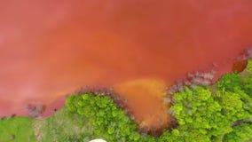 Vista aerea del fuco 4k dell'acqua di rame rossa variopinta dei rifiuti minerari contrariamente alla foresta verde fresca video d archivio