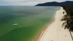 Vista aerea del fuco per inverdirsi oceano con la piccola barca e costa sabbiosa bianca con le piante tropicali in Tailandia Palm archivi video