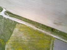 Vista aerea del fuco sulla strada nel campo Da un lato la terra aperta, con un altro un'erba Fotografie Stock