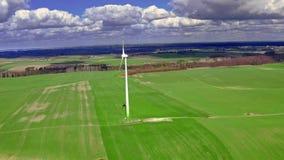 Vista aerea del generatore eolico bianco sul campo verde in primavera archivi video