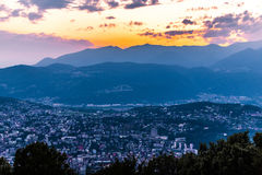 Vista aerea del lago di Lugano circondato dalle montagne e dalla città Lugano di sera sopra durante il tramonto drammatico, Svizz Immagine Stock
