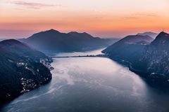 Vista aerea del lago di Lugano circondato dalle montagne e dalla città Lugano di sera sopra durante il tramonto drammatico, Svizz Fotografie Stock Libere da Diritti
