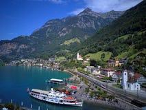 Vista aerea del lago Lucerna con una barca facente un giro turistico che gira sul lago, strade ferrate che allungano lungo la riv Immagine Stock Libera da Diritti