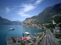 Vista aerea del lago Lucerna con una barca facente un giro turistico che gira sul lago, strade ferrate che allungano lungo la riv Fotografia Stock