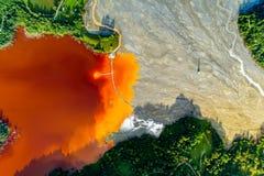 Vista aerea del lago del rifiuto tossico del villaggio di Geamana dalla miniera del coper fotografie stock