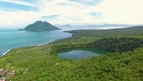 Vista aerea del lago tropicale Tolire e dell'isola di vulcano in Ternate, Indonesia archivi video